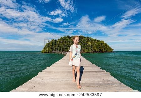 Little girl outdoors during summer vacation walking on footbridge from tropical island
