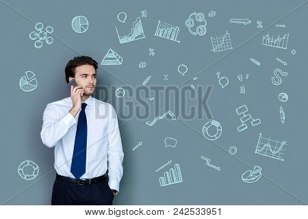 Serious Conversation. Young Successful Businessman Looking Serious While Talking On The Phone