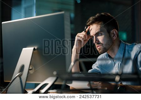 Man Focusing On Information In Computer Working Alone Late At Night In Modern Office.