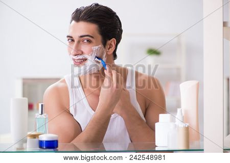 Young handsome man shaving early in the morning at home