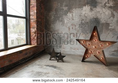 Large Decorative Retro Star With Lots Of Burning Lights On Grunge Concrete Background Near Window Fr