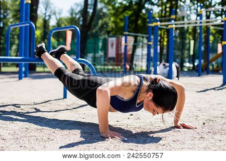 Young Sportive Trainer In A Bright Blue Sport Bra And Black Leggings Doing Push Ups On The Sport Pla