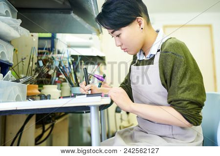 Side View Portrait Of Young Asian Woman Drawing Sketches In Glassworking Workshop, Ready To Create B