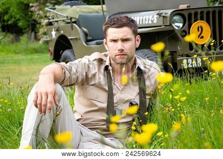American Wwii Gi Army Officer In Uniform Relaxes In A Meadow Of Flowers In Front Of Military Vehicle
