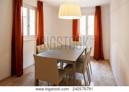 Elegant dining room with leather chairs. Two windows with red curtains. Nobody inside