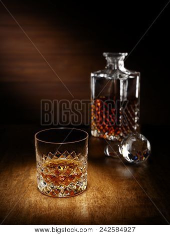 A Spotlight On A Single Crystal Glass Of Scotch Whisky With A Decanter In The Backghround, Shot On A
