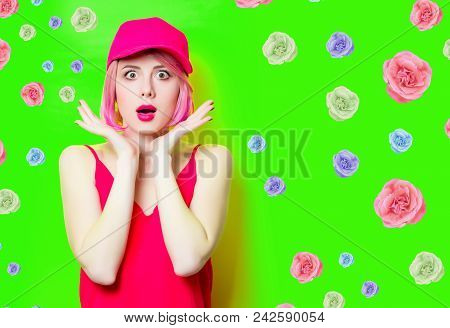 Portrait Of Beautiful Surprised Young Woman In Cap With Roses On The Wonderful Green Studio Backgrou