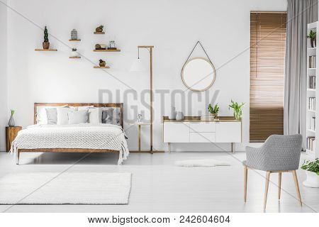 Spacious Designer White Bedroom Interior With Wooden Bed With Bedding And Pillows, Night-table, Smal
