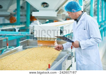 Side View Portrait Of Senior Factory Worker Doing  Production Quality Inspection In Food Industry Ho