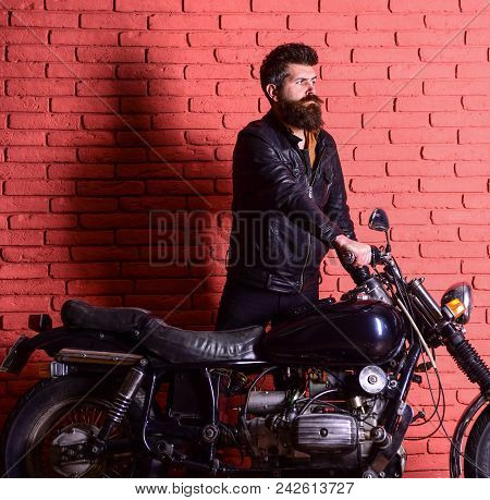 Hipster, Brutal Biker On Serious Face In Leather Jacket Gets On Motorcycle. Start Of Journey Concept