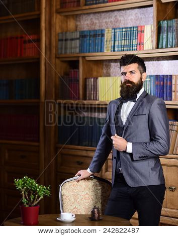Rich Man With Calm Face Looks Successful. Aristocrat Stands In Luxury Interior Near Empty Chair. Bea