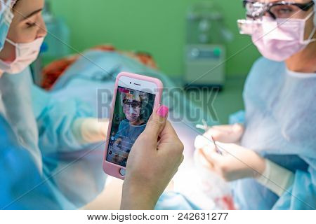 Surgeons Operating A Patient In An Operating Theater In A Hospital While Assistant Conducts A Live B