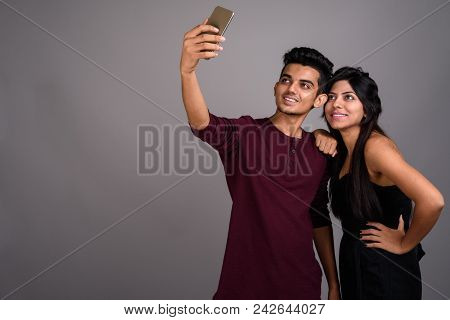 Studio Shot Of Young Indian Man And Young Indian Woman Together Against Gray Background