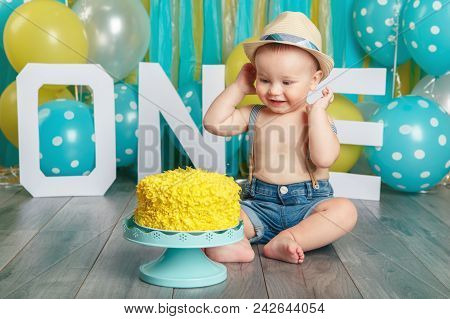 Portrait Of Cute Adorable Caucasian Baby Boy Wearing Jeans Pants And Hat Celebrating His First Birth