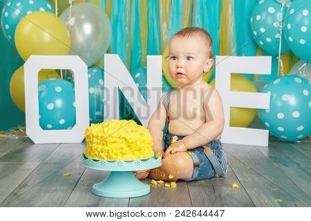Portrait of cute adorable Caucasian baby boy in jeans pants celebrating his first birthday. Cake smash concept. Child kid sitting on floor in studio eating tasty yellow dessert poster