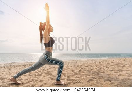 Woman Practicing Yoga On The Beach, Yoga And Meditation On The Calm Peaceful Beach At Sunset, Standi