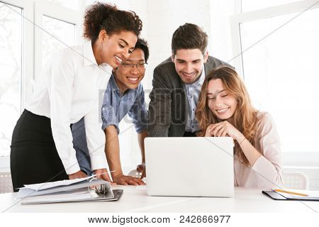 Group of cheerful young multiethnic businesspeople discussing ideas while looking at laptop computer