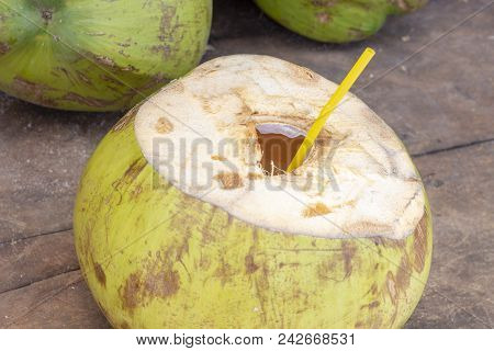 Opened Coconut With Straw Ready For Drinking. Fresh Coco Water Photo. Coconut Fruit On Wooden Table.