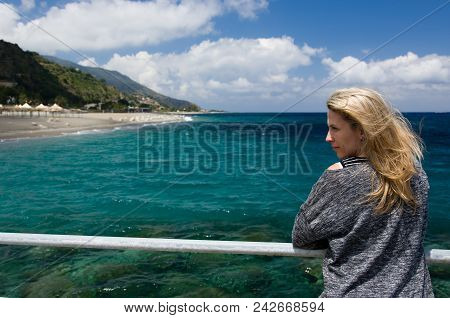 Blonde woman outdoor, azure blue sea background, beach and mountan