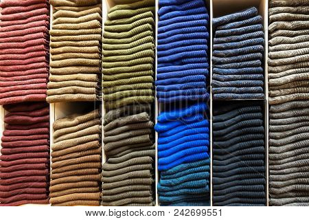 Wooden Shelves With Stack Of Different Color Socks In A Clothing Store.