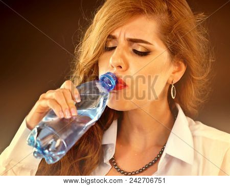 Sensitive teeth woman drinking cold water from bottle. Sudden toothache of thirsty girl in business suit drink. Lady with closed eyes guzzles on black background. Grimace hurts on face.