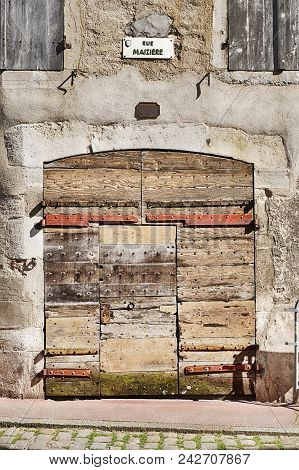 An Old Garage Door Made Of Many Pieces Of Wood Has Endured Centuries Of Weather On Rue Maziere In Th