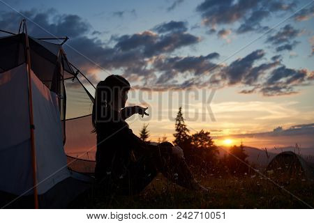 Attractive Woman Sits In A Profile Near A Tent On The Grass With Wildflowers And Shows Her Hand In T