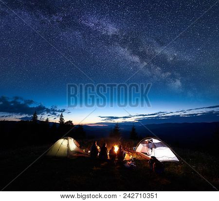 Family Tourists Mother, Father, Two Guys Resting At Night Camping In Mountains, Sitting On Log Besid