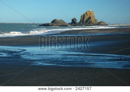 Wild Ocean Beach With Rock Island And Lighthouse