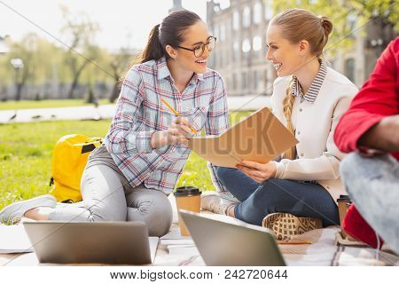 Studying Outside. Two Pleasant Good-looking Students Enjoying Their Time While Studying Outside Toge