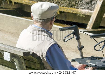 An Old Man Is Sitting On A Bench In The Park