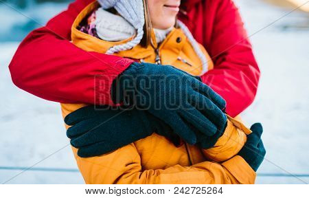 Man In Red Jacket And Woman In Yellow Jacket Are Hugging. Hugs From Behind. Close-up