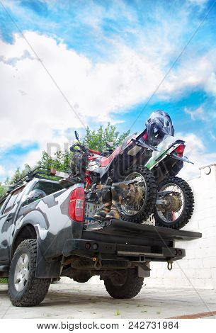 Two Dirt Bike Motorcycles On The Back Of The Camo Truck With Safety Equipment, Such As Motorcycle Bo