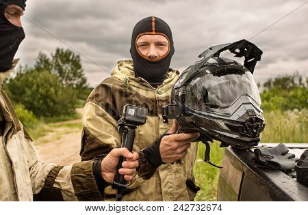 Close Up Of Two Men Outdoors Wearing Balaclava Helmets And Motorcycle Uniforms, One Man Is Holding S