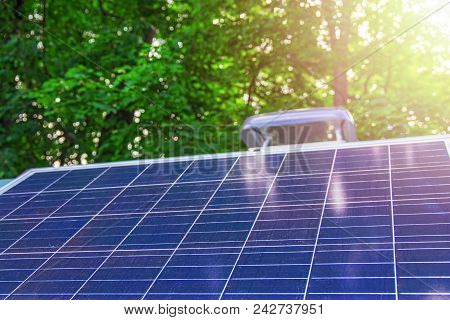 Solar Panels On A Background Of Green Foliage And Sunlight. The Concept Of Renewable Energy, Environ