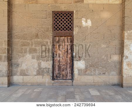 Facade Of Old Abandoned Stone Bricks Wall With One Weathered Wooden Door And Wooden Grid Window, Old
