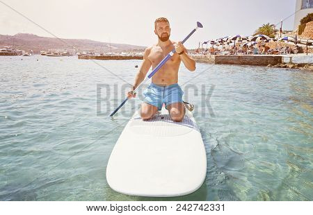 Adult Bearded Man Beginner Surfer Kneel On Paddle Board On Sea. Summer Active Vacation And Water Spo