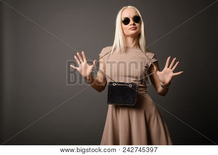 Beautiful Girl With A Handbag And Sunglasses Shows Palms Isolated On Grey Background