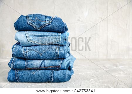 Stack Of Blue Jeans On A Gray Background A