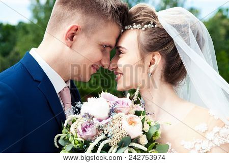 Bride And Groom In Park. Kissing Couple Newlyweds Bride And Groom At Wedding In Nature Green Forest