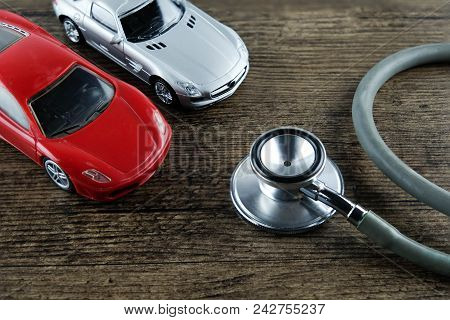 Stethoscope And Car On The Wooden Background, Concept Of Car Check-up, Repair And Maintenance..