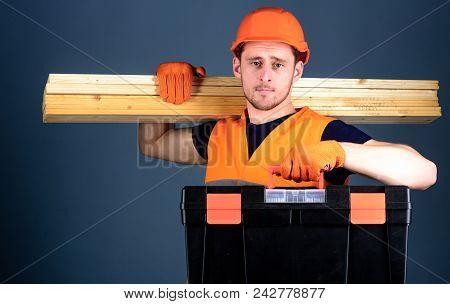 Carpenter, Labourer, Builder, Woodworker On Calm Face Carries Wooden Beams On Shoulder. Professional