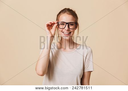Portrait of cute blond woman 20s wearing basic t-shirt touching eyeglasses and smiling at camera with white perfect teeth isolated over beige background in studio poster