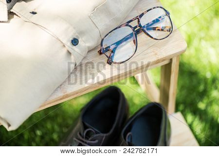 Selective Focus Of Arranged Eyeglasses, Leather Shoes And Male Shirt On Wooden Stairs On Grassland