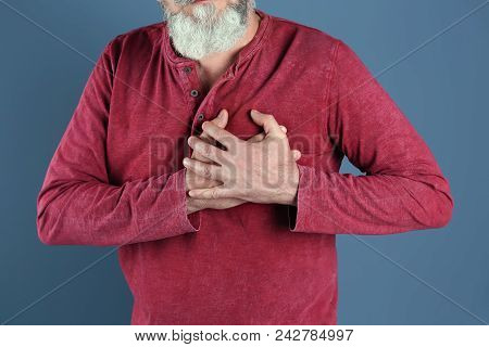 Mature Man Having Heart Attack On Color Background, Closeup