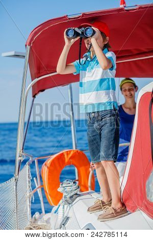 Boy Captain With His Sister On Board Of Sailing Yacht On Summer Cruise. Travel Adventure, Yachting W