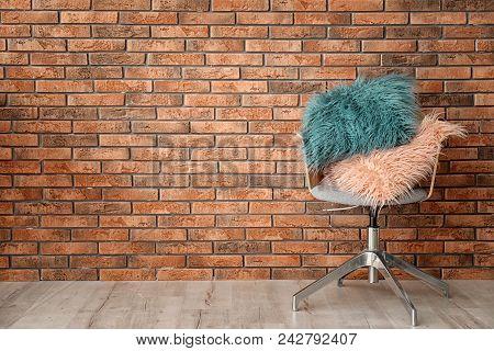 Fuzzy pillows on armchair near brick wall poster
