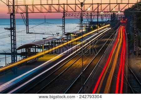 Aerial View Of The Railway Station With Motion Blurred Trains On The Background Of The Sea At Sunset