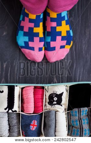 Feet Selfie With Colorful Socks And A Socks Organizer On A Dark Wooden Background. Top View