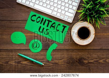 Contact Us Concept. Lettering Contact Us Near Phone And Email Signs On Office Work Desk With Compute